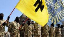 """Miembros del batallón Azov, creado por el régimen de Kiev, portan una bandera con el símbolo conocido en alemán como Wolfsangel (""""gancho para lobos""""), utilizado durante la Segunda Guerra Mundial como emblema de la división Das Reich perteneciente a las Waffen SS. Ese mismo símbolo identifica también a la organización ucraniana de extrema derecha Pravy Sektor   Red Voltaire"""