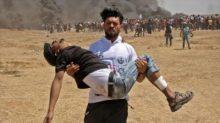 Un palestino traslada a un palestino herido durante las marchas antisraelíes en Gaza, 14 de mayo de 2108